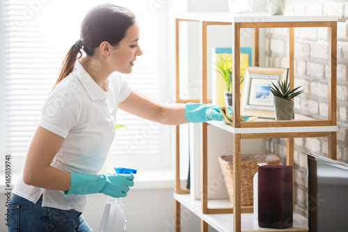 Young Woman Cleaning The Shelf In House - 165039741