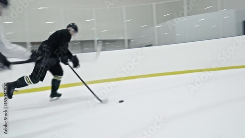 Tracking of ice hockey players from opposite teams fighting for puck during practice in rink; forward in white uniform scoring goal
