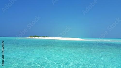 P00552 Maldives beautiful white sandy beach background on sunny tropical paradise island with aqua blue sky sea water ocean 4k