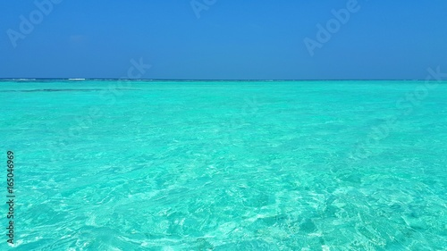 P00589 Maldives beautiful white sandy beach background on sunny tropical paradise island with aqua blue sky sea water ocean 4k