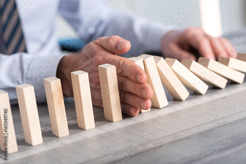 Concept of business control by stopping domino effect - 165049740