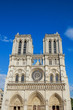 Notre Dame de Paris central main facade, national monument cathedral of France. French Gothic architecture. Sunny blue cloudy sky.