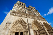 Notre Dame Gothic cathedral in Paris, France in sunny blue sky. Our Lady of Paris church with no people. Details close up bottom point of view. Popular tourist religious attraction in Paris and France