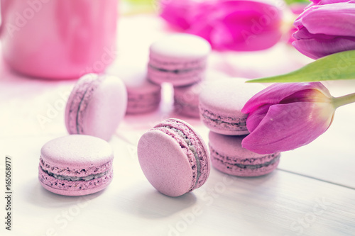 Violet sweet delicious macaroons and fresh tulips on white background. Cup of hot tea. Shallow depth of field. Coloring toned photo.