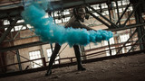 A girl in a gas mask and latex posing with colored smoke at a ruined factory magnificent advertising of colored smoke