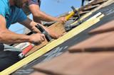 couvreurs clouant des lattes pour rénovation toiture - 165081763