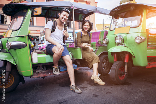 couples of young traveling people sitting on tuk tuk bangkok thailand Poster