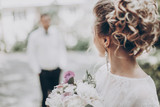 stylish wedding bride with bouquet and amazing modern dress. bride posing and looking at groom in sunny garden, fine art wedding photo, romantic moment, long edge - 165104181