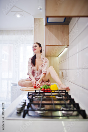 Happy young woman in pink robe sitting on the surface and making the salad.