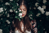 sensual calm portrait of beautiful hipster woman in blooming bush with white flowers of spirea. boho girl sensual portrait in floral modern clothes in greenery. space for text - 165109753