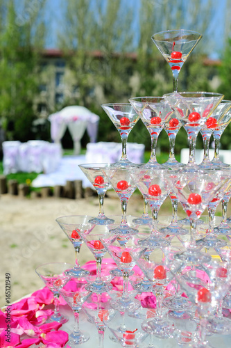 Champagne slide outdoors against a wedding arch and greens