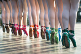 Ballerinas feet dancing on ballet shoes with several colors on stage during a performance. - 165168395