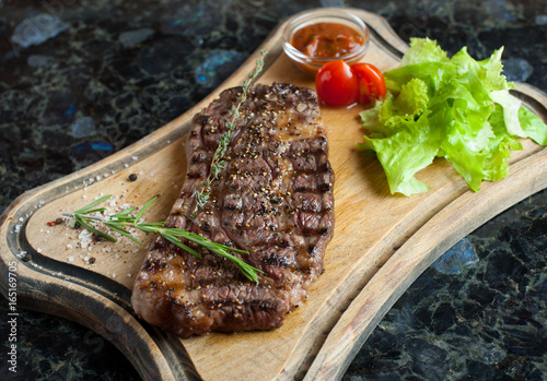 Juicy steak from marbled beef on a wooden board