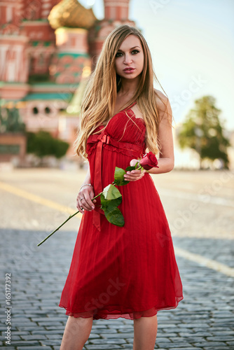 Beautiful blonde lady in red dress on Red Square in Moscow, Russia