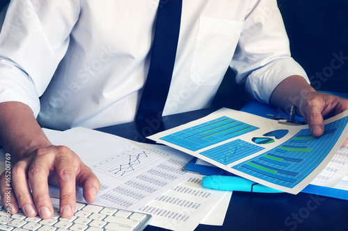 Businessman working with computer and financial business documents at office.