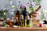 Selection of essential oils with herbs and flowers - 165219792