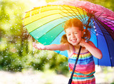 Happy child girl laughs and plays under summer rain with an umbrella. - 165224115