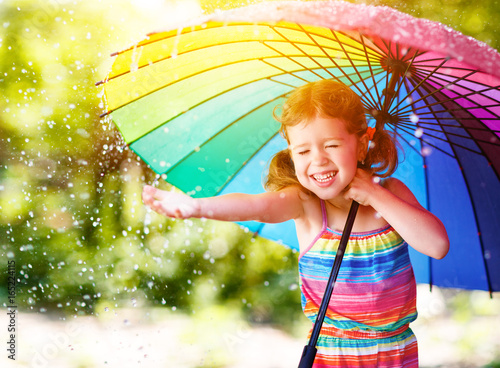 Fototapeta Happy child girl laughs and plays under summer rain with an umbrella.
