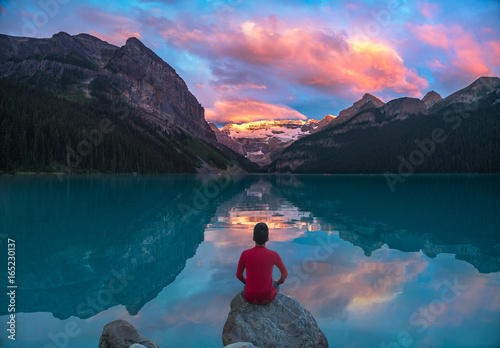 Staande foto Canada Man in red sit on rock watching Lake Louise morning clouds with reflections