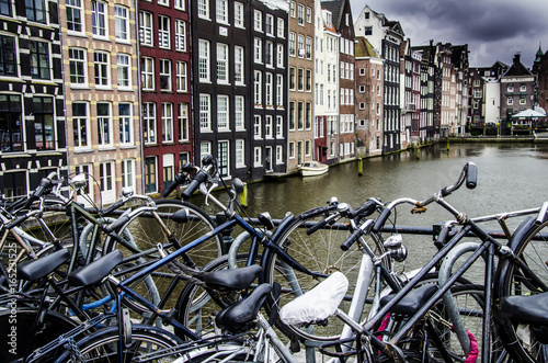Symbols of amsterdam bicycles and boat moored in one of its canals Poster