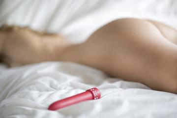 femme nue couchée sur un lit avec un vibromasseur