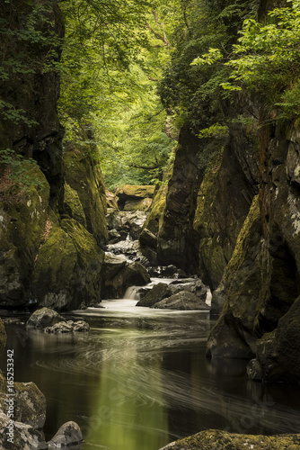 Stunning landscape with river flowing through deep sided gorge with vibrant green foliage