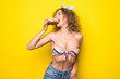 Comic slim hipster woman eating  donuts on yellow background