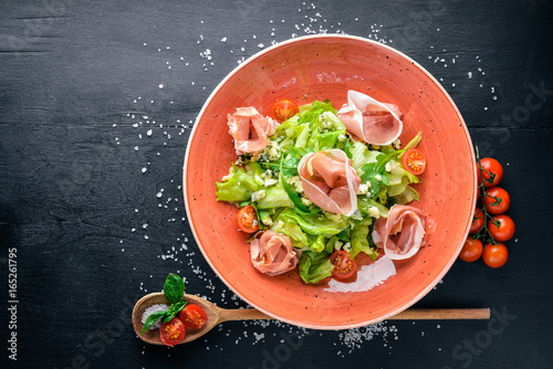 Salad of fresh vegetables and bacon. Caesar. On a wooden background. Top view. Free space for your text.