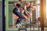 Fototapety Male and female athletes doing box jumps at gym