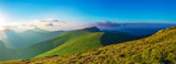 Panorama of mountain ridges with clouds and fog in the morning evening time, at sunrise, sunset