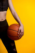 Cropped rear view of girl basketball player holding a basketball on  yellow background.basketball ball in hands