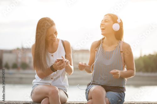 Two happy women are having fun together in the city. They are listening music.