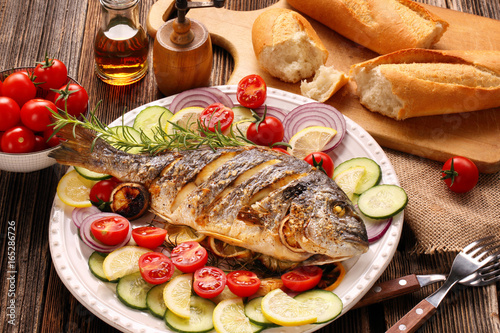 Roasted dorada fish with vegetables on wooden background - 165286726
