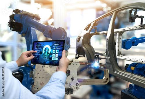 Inżynier ręcznie za pomocą tabletu z oprogramowaniem systemu monitorowania w czasie rzeczywistym maszyny. Automatyzacja robot ramię maszyny w inteligentnej fabryce motoryzacyjnej Przemysł przemysłowy 4. iot, cyfrowa produkcja operacji.