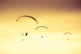 Colorful hang glider/paraglider against the colorful sunset sky  - 165318959