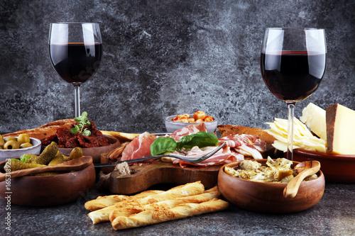 Italian antipasti wine snacks set. Cheese variety, Mediterranean olives, pickles, Prosciutto di Parma, tomatoes, artichokes and wine in glasses - 165318923