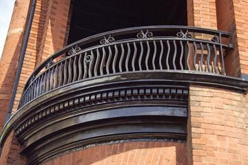Ornate ironwork curved balcony with brick building. Savannah, Georgia.