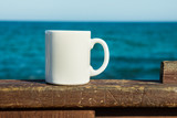 White mug, mock up, empty space for artwork, text, standing on wood plank, turquoise sea, clear blue sky, horizon, sunlight, nature - 165330151