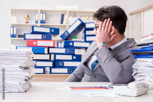 Businessman busy with much paperwork - 165355313