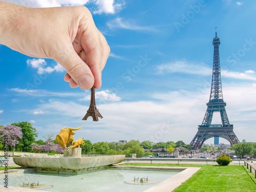 Eiffel Tower model in man's hand against Eiffel Tower