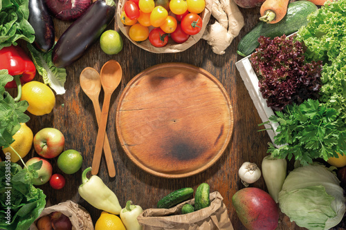 Around round kitchen board set of fresh vegetables and fruits - 165385580