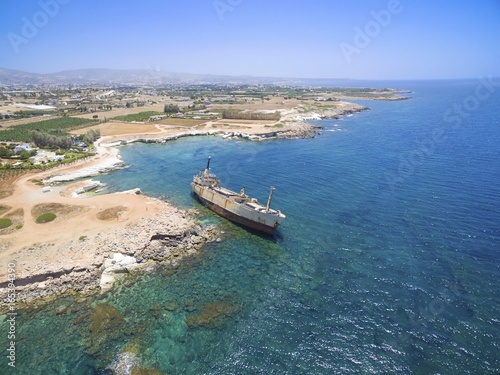 Foto op Plexiglas Cyprus Aerial view of abandoned ship wreck EDRO III in Pegeia, Paphos, Cyprus. The rusty shipwreck is stranded on Peyia rocks at kantarkastoi sea caves, Coral Bay, Pafos, standing at an angle near the shore.