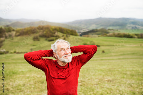 Active senior runner in red sweatshirt in nature resting.