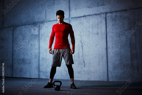 Poster Athlete standing before kettlebell workout