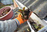 Rain Gutter Cleaning from Leaves in Autumn with hand. Roof Gutter Cleaning Tips. Clean Your Gutters Before They Clean Out Your Wallet. Gutter Cleaning. - 165418950
