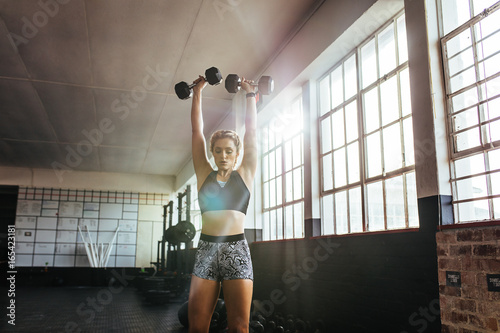 Young woman working out at the gymnasium using dumbbells.