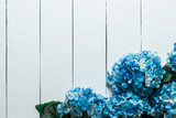 Blue hydrangea flowers on a white wooden texture background.Artificial Flowers - 165427372