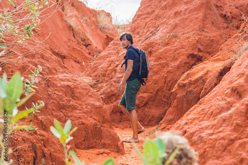 Fotobehang Koraal Young man in red canyon near Mui Ne, southern Vietnam