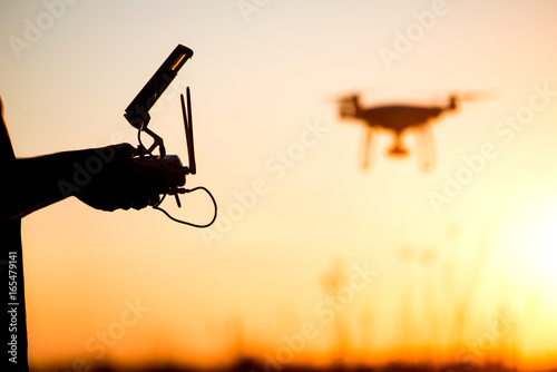 Fototapeta Young man operating of flying drone the setting sun
