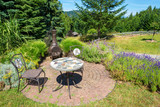 Rustic patio table in a lush garden with lavender plants. - 165487125